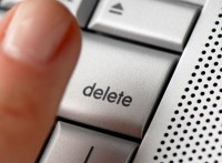 A woman's finger hovering over the delete key